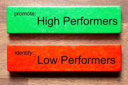 green block with text: promote: High Performersred block with text: identify: Low PerfomersThe background is a dark wooden table