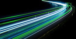 green, blue and white car lights on the road at night
