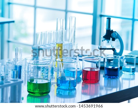 green, blue, red , and dark blue color liquid in glass beaker and yellow one in tube at the laboratory for researchers to do their work.