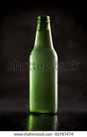 Green bottle of beer on a dark background