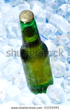 Green bottle of beer on ice cold background