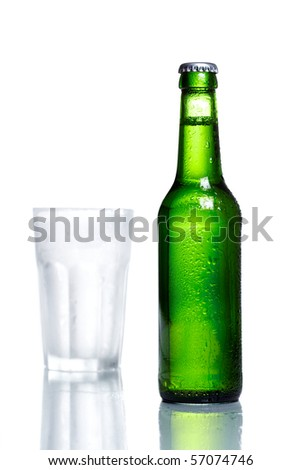 Green bottle of beer with drops in front of a frozen glass