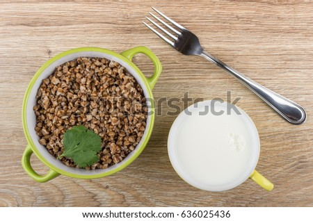 Green bowl with boiled buckwheat, cup of milk and fork on wooden table. Top view #636025436