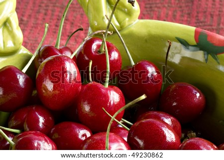 Green bowl with handle filled with ripe red cherries