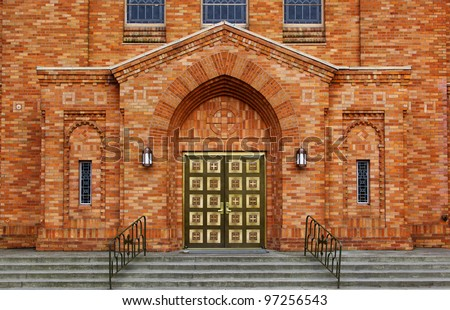 Green brass doors and orange brick facade of the front of a Greek Orthodox Church