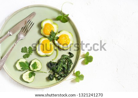 green breakfast on St. Patrick's Day. eggs in the form of clover. Fried Eggs Shamrock  in Green Pepper rings with Braised Spinach. parsley leaves like clover leaves. copy space. top view.