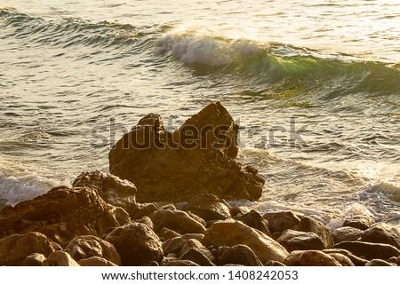 green breaking wave on rocky shoreline in california