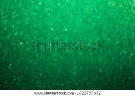 Green bright abstract background with bokeh. Festive sparkles, magic backdrop