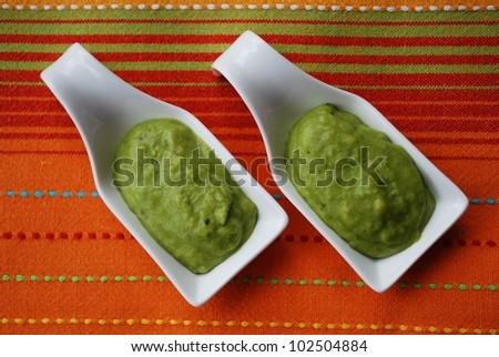 Green broad beans cream with basil in white china dish on orange fabric background
