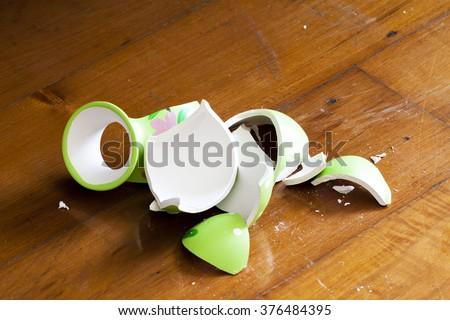 green broken vase on wooden floor #376484395