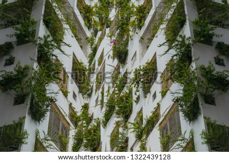 Green building architecture background. Building with green plants in windows. Sustainable, green architecture #1322439128