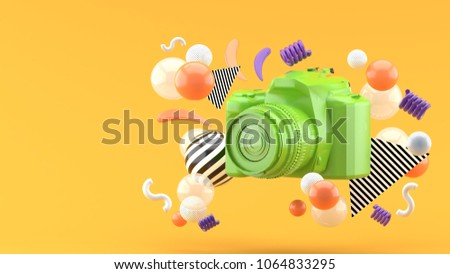 Stock Photo Green camera surrounded by colorful balls on an orange background.-3d render.