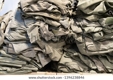 green camouflage surplus of military clothes in the store for sale