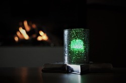 Green Candle In The Silver Glass On The Table And Fire Flame Of Fireplace. Light And Darkness Background.