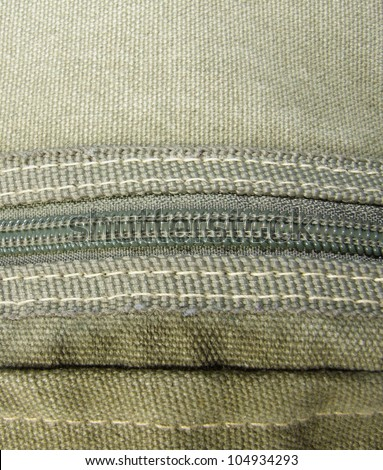 Green canvas fabric with zipper and stitching