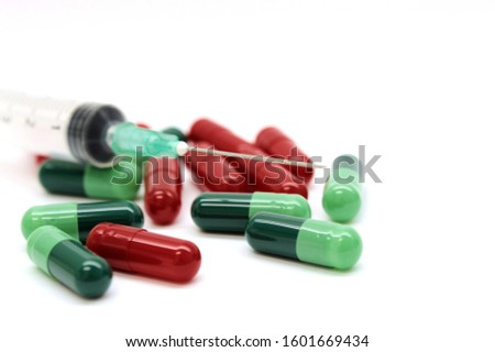 Green capsules red capsules and a syringe isolated on white background