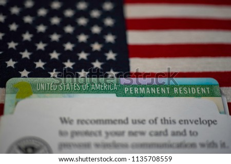 Green card (permanent resident) in paper USCIS envelope  on flag of USA.