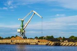 Green cargo crane in terminal in river ship port in Ventspils, Latvia, Baltic sea. Shipping import or export, logistic. Storage, port cranes, industrial scene. Venta river.