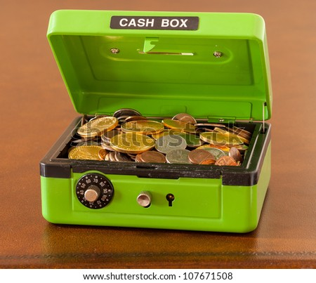 Green Cash Box With Combination Lock Open To Show Piles Of