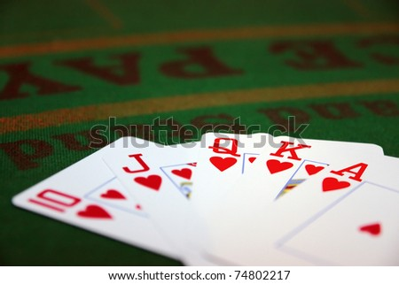 green casino table with a hand of a royal flush in a poker game