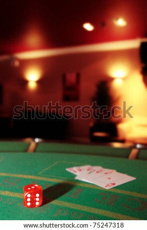 green casino table with dice and a hand of a royal flush in a poker game