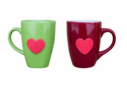 Green ceramic mug and maroon ceramic mug decorated with red heart, on white background, close-up