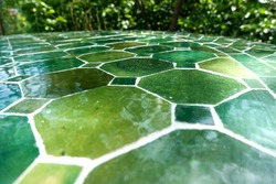 Green ceramic tiles in different shades on a table in lush summer garden