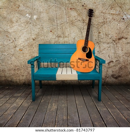 Green chair and acoustic quitar in a grunge room with wooden floor