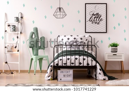 Green chair next to kid's bed and ladder against wallpaper with cactus in bedroom interior with poster #1017741229