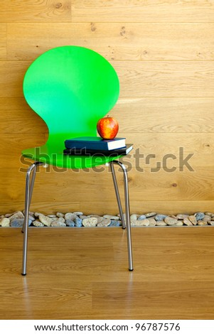 Green Chair, Red Apple and some Books against wooden wall / Modern interior