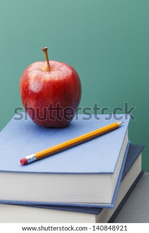 Green Chalkboard, Books and Apple in Classroom Setting with Copy Space.