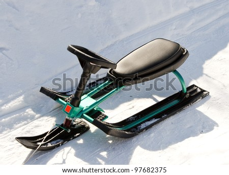 Green Children's sled (snowmobile, snowbicycle). The photo was taken near Moscow.