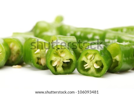 Green chili pepper cut in pieces on a white background
