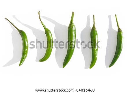 green chilis in sunlight with shadows isolated on white background