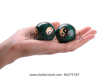 Green Chinese balls for relaxation on woman hand on white background