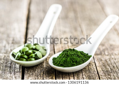 Green chlorella pills or green barley pills and powder in ceramic spoon.