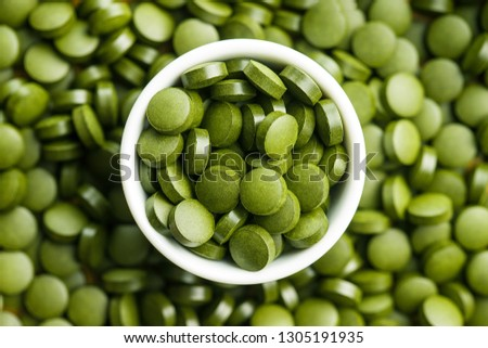 Green chlorella pills or green barley pills in bowl. Top view.