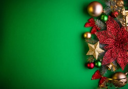 Green Christmas background with fir tree, toys and poinsettia