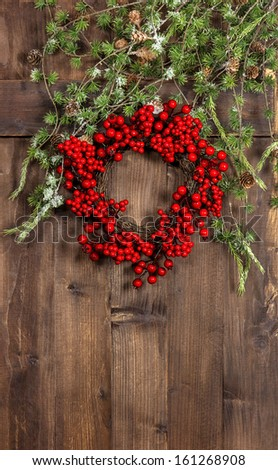 Green christmas tree branches and wreath from red berries over rustic