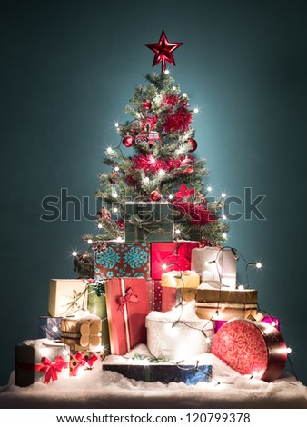 green christmas tree with beatiful red decorations surrounded by a heap of gift boxes covered with snow o blue gradient background