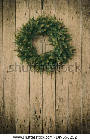 Green Christmas Wreath on a wooden planks,toned
