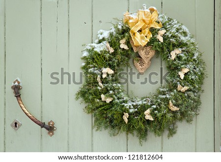Green Christmas wreath with a golden bow on a wooden green rustic door