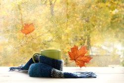 green circle in the scarf, the window with maple leaves and drops after rain in autumn / season when you need warm drinks