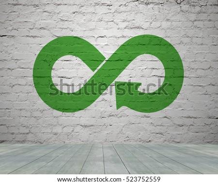 Green circular economy concept. Arrow infinity symbol with grass on brick wall. #523752559