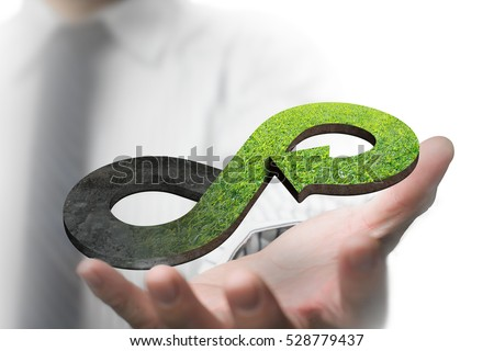 Green circular economy concept. Hand showing arrow infinity symbol with grass texture. #528779437