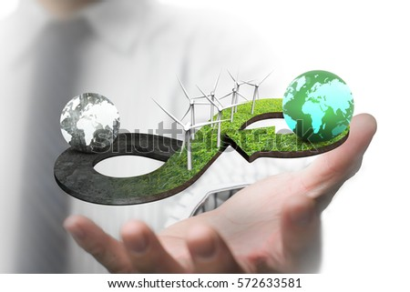 Green circular economy concept. Man's hand showing arrow infinity symbol of grass texture with wind turbines and two globes of different colors. #572633581