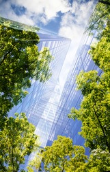 green city - double exposure of lush green forest and modern skyscrapers windows
