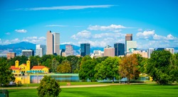 Green City Park View of Denver Colorado downtown skyline rising behind green city park tree line with Rocky Mountain background wide panoramic view
