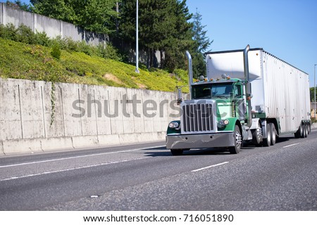 Green classic big rig semi truck with tall exhaust chrome pipes and heavy duty roomy bulk semi trailer transporting industrial processing cargo on divided highway with cascade concrete wall #716051890