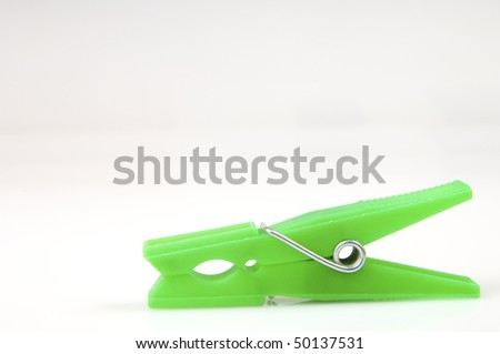 Green cloth peg isolated in a white background